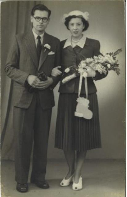 Rosetta and Michael on their wedding day. Rosetta holds a bouquet of flowers, wearing a two-piece suit and skirt with white shoes and pearls. Michael has glasses, and wears a suit and thick rimmed glasses.