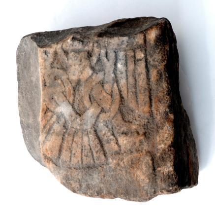 A small fragment square rock, the front has a pattern faintly etched on and you can just make out a pair of legs.