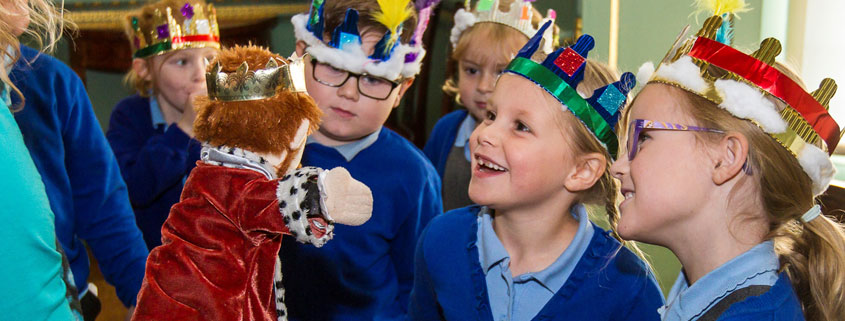Primary school children and smiling and laughing whilst interacting with a teacher who is using a hand puppet dressed up as a king