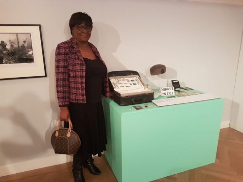 Image of former midwife Gloria Hanley with the items she has loaned to the exhibition
