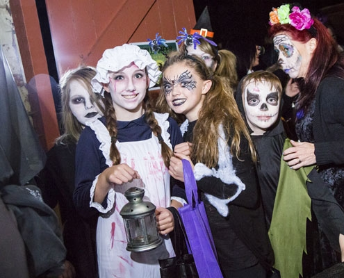 A group of children dressed up in various costumes for Halloween and smiling at the camera
