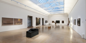 A bright white gallery space with glass roof filled with contemporary artworks and sculpture