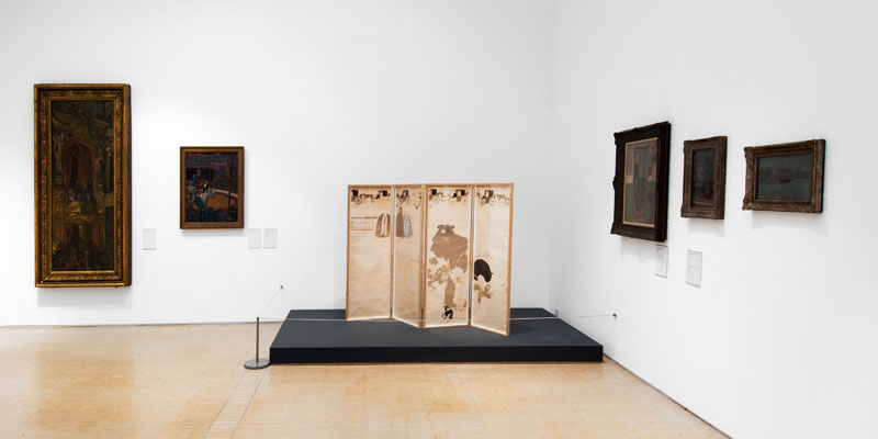 A display of artworks framed and hung in a gallery and an oriental style screen on display on a raised plinth