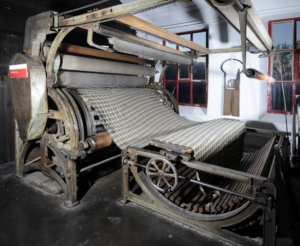 A large old machine with two wheels and a large piece of material running through them