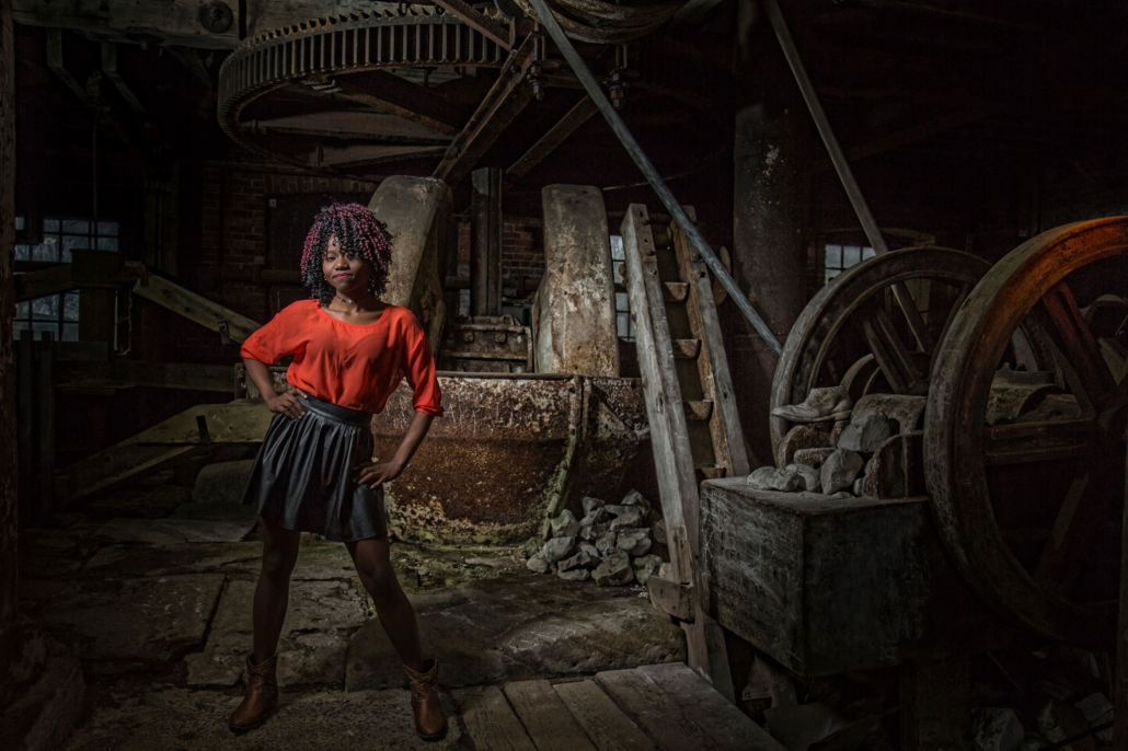 A girl is posing against an industrial backdrop in an old mill setting
