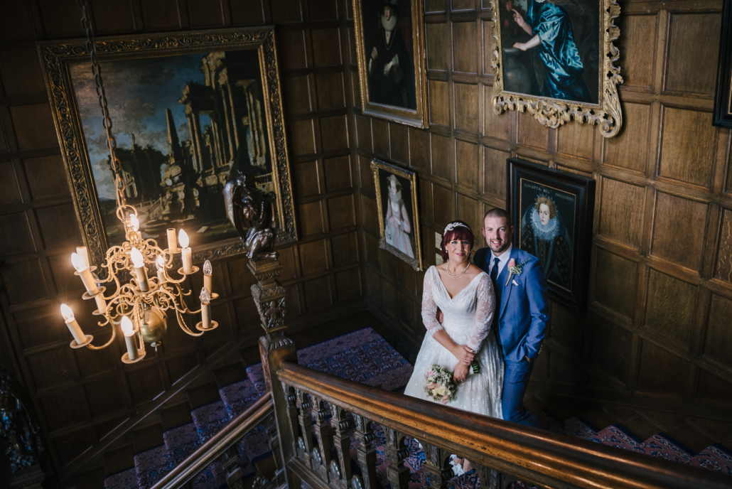 A wedded couple pose on the ok staircase of Temple Newsam House