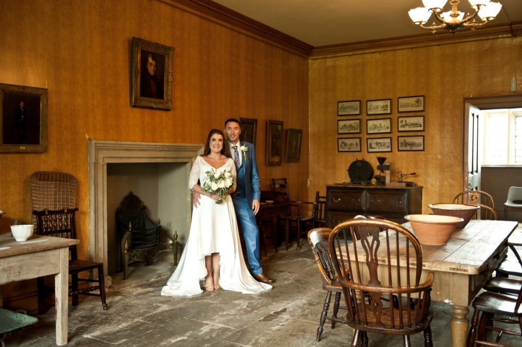 A wedding couple pose in the Still Room of Temple Newsam House