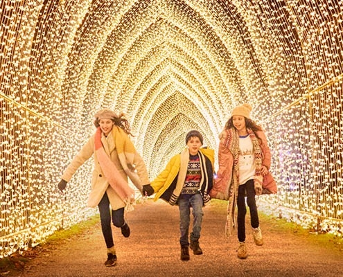 3 children including two girls and a boy run through a Christmas light tunnel wearing winter clothing