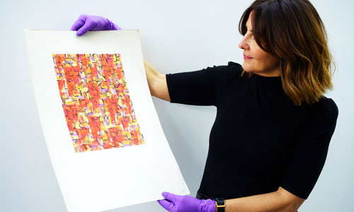 A woman holds a Sheila Bownas print