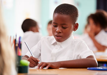 A boy writing on a piece of paper