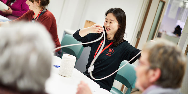 A member of staff works on crafts activities in Leeds Art Gallery. She looks happy as she chats to guests